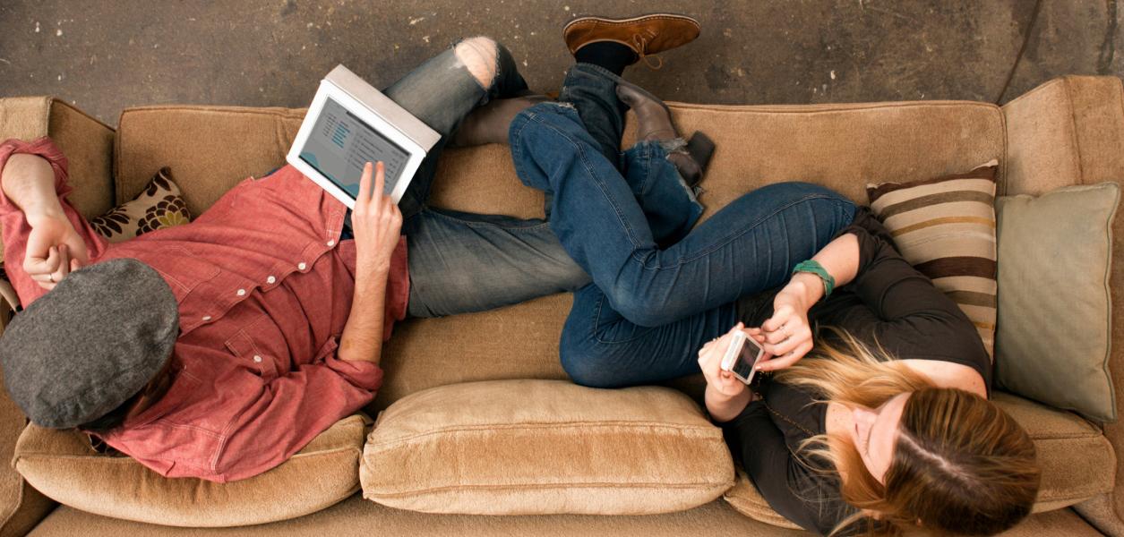 Chicos utilizando Fintonic en el sofá. (Aplicación de finanzas personales, economía doméstica, ahorrar, control, dinero, casa, excel, cuentas, banco. App para iOS, iphone, iPad, Android, fácil y gratis, organizar, gastos, ingresos, gráfico, presupuesto, alertas)